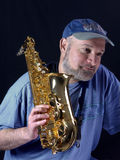 Saxophone player resting. Tired saxophone player, holding the instrument on his shoulder. Black background, lateral light Stock Images