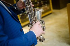 Saxophone player. Saxophonist hands playing saxophone. Alto sax player with jazz music instrument closeup.  Stock Photos