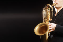 Saxophone. Jazz musical instruments Saxophonist with Baritone sax details closeup on black Royalty Free Stock Photography
