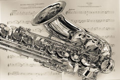 Saxophone. On sheet music with detail off valves and trumpet royalty free stock photos