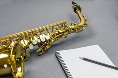 Saxophone Song Writing. Close up shot of an alto saxophone and pen symbolizing creativity while writing a song Stock Images