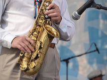 Saxophone on stage. Color photo of a man with a saxophone on stage Stock Image