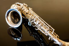 Saxophone tenor. Woodwind Classical Instrument. Jazz, blues, classics. Music. Saxophone on a black background. Black mirror surfac Royalty Free Stock Photography