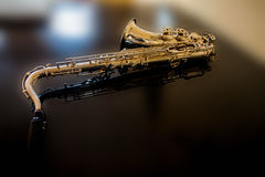 Saxophone tenor. Woodwind Classical Instrument. Jazz, blues, classics. Music. Saxophone on a black background. Black mirror surfac Stock Photography