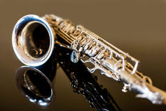 Saxophone tenor. Woodwind Classical Instrument. Jazz, blues, classics. Music. Saxophone on a black background. Black mirror surfac Stock Photos