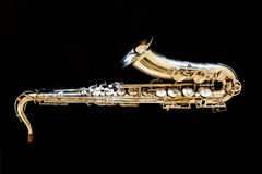 Saxophone tenor. Woodwind Classical Instrument. Jazz, blues, classics. Music. Saxophone on a black background. Black mirror surfac Royalty Free Stock Photo