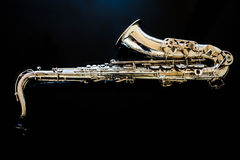 Saxophone tenor. Woodwind Classical Instrument. Jazz, blues, classics. Music. Saxophone on a black background. Black mirror surfac. Musical instrument saxophone Royalty Free Stock Images