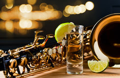 Saxophone and tequila with lime. On wooden table Royalty Free Stock Photo