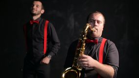 Saxophone and trumpet players vintage retro style. Musicians stock footage