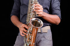 Saxophone view with hands playing it, view of the front Royalty Free Stock Image