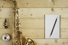 Saxophone on the Wood Background. With mouse, mute, pencil and notebook Royalty Free Stock Images