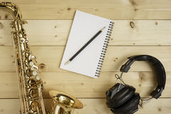 Saxophone on the Wood Background. With pencil, notebook and headphones Royalty Free Stock Photography