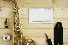 Saxophone on the Wood Background. With strap, mouse, mute, pencil and notebook Royalty Free Stock Image
