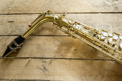 Saxophone. The saxophone on wooden background royalty free stock images