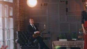 Saxophonist στην καρέκλα στη σκηνή Ο αοιδός της Jazz αποδίδει στο μικρόφωνο φω'τα απόθεμα βίντεο