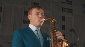 Saxophonist στην μπλε κομψή τζαζ παιχνιδιού κοστουμιών στο χρυσό saxophone στο στάδιο μουσική απόθεμα βίντεο