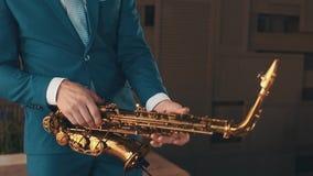 Saxophonist στην μπλε τζαζ παιχνιδιού έναρξης κοστουμιών στο χρυσό saxophone στο στάδιο κομψότητα απόθεμα βίντεο