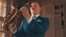 Saxophonist στην μπλε τζαζ παιχνιδιού κοστουμιών στο χρυσό saxophone με το μικρόφωνο κομψότητα φιλμ μικρού μήκους