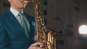 Saxophonist στην μπλε τζαζ παιχνιδιού κοστουμιών στο χρυσό saxophone με το μικρόφωνο μουσική φιλμ μικρού μήκους