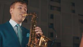Saxophonist στην μπλε τζαζ παιχνιδιού κοστουμιών στο χρυσό saxophone στο στάδιο μουσική καλλιτεχνών απόθεμα βίντεο
