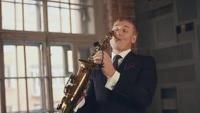 Saxophonist στη μαύρη τζαζ παιχνιδιού κοστουμιών στο χρυσό saxophone Αοιδός στη σκηνή απόθεμα βίντεο