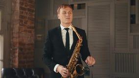Saxophonist στη στάση σακακιών γευμάτων στη σκηνή με το χρυσό saxophone Καλλιτέχνης της Jazz απόθεμα βίντεο