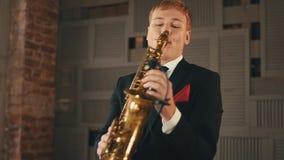Saxophonist στη στάση σακακιών γευμάτων στη σκηνή με το χρυσό saxophone Μουσικός της Jazz απόθεμα βίντεο