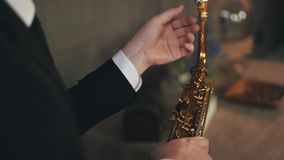 Saxophonist στη συνεδρίαση σακακιών στην καρέκλα με το χρυσό saxophone Καλλιτέχνης της Jazz απόθεμα βίντεο