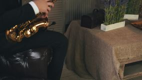 Saxophonist στη συνεδρίαση σακακιών στην καρέκλα με το χρυσό saxophone τζαζ Στάση επάνω απόθεμα βίντεο