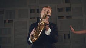 Saxophonist στο μαύρο παιχνίδι κοστουμιών στο χρυσό saxophone με το μικρόφωνο Μουσική της Jazz απόθεμα βίντεο