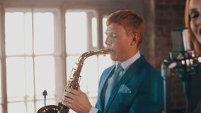 Saxophonist στο μπλε παιχνίδι κοστουμιών στο χρυσό saxophone Ζήστε απόδοση τζαζ απόθεμα βίντεο