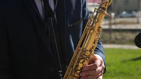 Saxophonist στο παιχνίδι σακακιών γευμάτων στο χρυσό saxophone Ζήστε απόδοση μια παίζοντας μουσική τζαζ saxophone ατόμων απόθεμα βίντεο