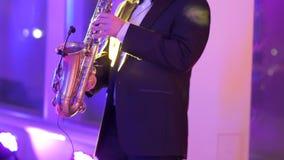 Saxophonist στο παιχνίδι σακακιών γευμάτων στο χρυσό saxophone απόθεμα βίντεο