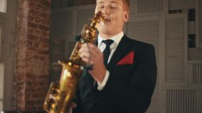 Saxophonist στο παιχνίδι σακακιών γευμάτων στο χρυσό saxophone στο στάδιο Καλλιτέχνης της Jazz φιλμ μικρού μήκους