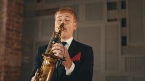 Saxophonist στο σακάκι γευμάτων στη σκηνή με το χρυσό saxophone Μουσική καλλιτεχνών της Jazz απόθεμα βίντεο