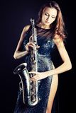 Saxophonist. Portrait of a sexual young woman posing with saxophone at studio Royalty Free Stock Photography