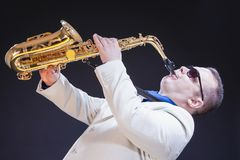 Saxophonist Against Black Background. Horizontal Image Orientation. Music Themes and Ideas. Passionate Caucasian Mature Saxophonist Against Black Background Royalty Free Stock Photography