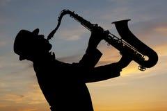 Saxophonist bei Sonnenuntergang Stockfotos