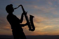 Saxophonist bei Sonnenuntergang Stockbilder