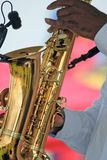 Saxophonist Plays Against Multicolored Backg Stock Image