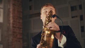 Saxophonist in black suit play jazz on golden saxophone with microphone. Music. Live performance stock video footage