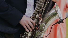 Saxophonist in black suit play jazz on golden saxophone with microphone. Music. Live performance stock video