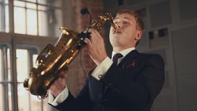 Saxophonist in black suit play jazz on golden saxophone. Musician. Performing stock footage