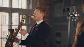 Saxophonist in black suit with vocalist in dark dress on stage. Duet. Jazz music. Retro style stock footage