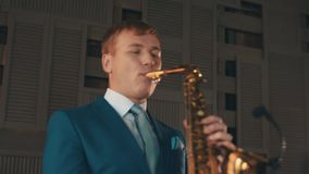 Saxophonist in blue elegant suit play jazz on golden saxophone at stage. Music stock video footage
