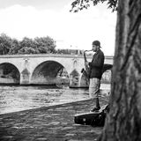 Saxophonist in border Seine river in Paris Stock Image