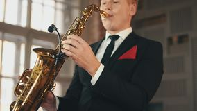 Saxophonist in dinner jacket play jazz on golden saxophone at stage. Music. stock video footage