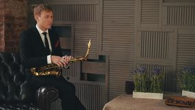 Saxophonist in dinner jacket sitting on chair with golden saxophone. Jazz artist. Instrument. Concert stock footage