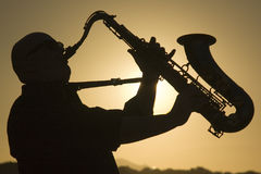 Saxophonist at dusk 2. A saxophonist playing on the beac in Famara in Lanzarote royalty free stock image