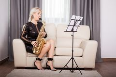 Saxophonist girl playing at her musical instrument in the living Stock Photos